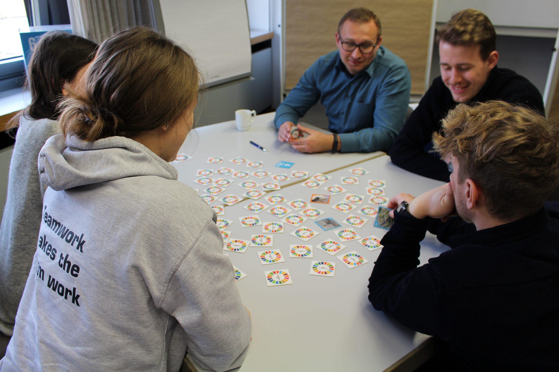 Gruppe junger Menschen spielt SDG - Memo